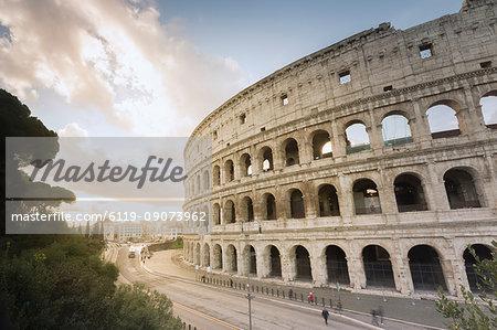 The lights of sunrise frame the ancient Colosseum (Flavian Amphitheatre), UNESCO World Heritage Site, Rome, Lazio, Italy, Europe