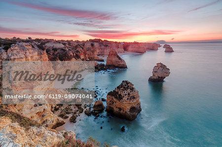 Sunrise on cliffs framed by turquoise water of the ocean, Praia da Marinha, Caramujeira, Lagoa Municipality, Algarve, Portugal, Europe