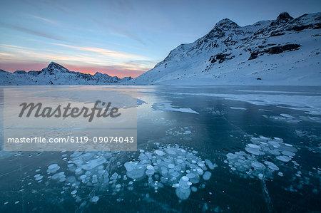 Ice bubbles frame the snowy peaks reflected in Lago Bianco, Bernina Pass, canton of Graubunden, Engadine, Switzerland, Europe
