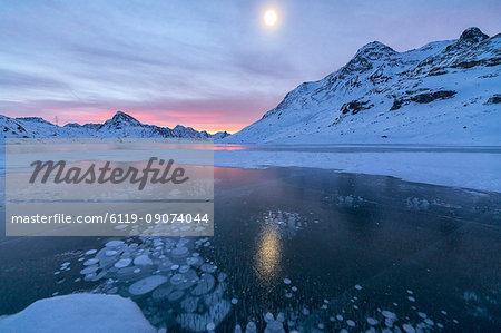 Ice bubbles frame the frozen Lago Bianco at dawn, Bernina Pass, canton of Graubunden, Engadine, Switzerland, Europe