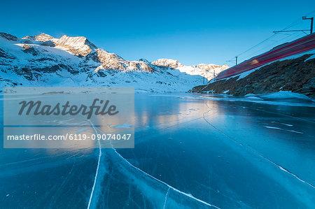The Bernina Express train runs beside the frozen Lago Bianco, Bernina Pass, canton of Graubunden, Engadine, Switzerland, Europe