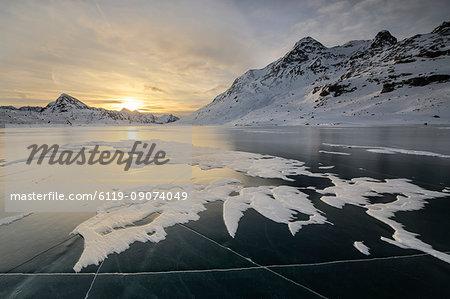 The frozen surface of Lago Bianco framed by snowy peaks at dawn, Bernina Pass, canton of Graubunden, Engadine, Switzerland, Europe