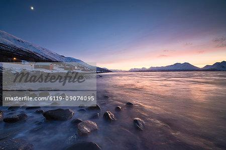 Fiery sky at sunset on typical Rorbu framed by snowy peaks and frozen sea, Djupvik, Lyngen Alps, Troms, Norway, Scandinavia, Europe