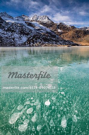 Ice bubbles in the turquoise water of the frozen White Lake (Lago Bianco), Bernina Pass, Canton of Graubunden, Engadine, Switzerland, Europe