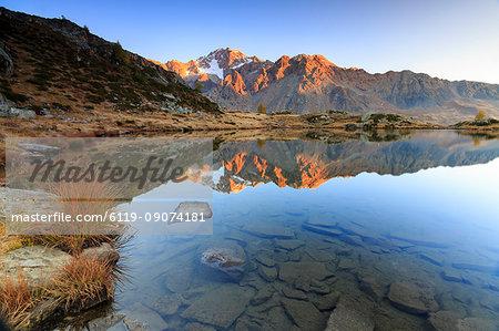 Rocky peaks of Mount Disgrazia reflected in Lake Zana at sunrise, Malenco Valley, Valtellina, Lombardy, Italy, Europe