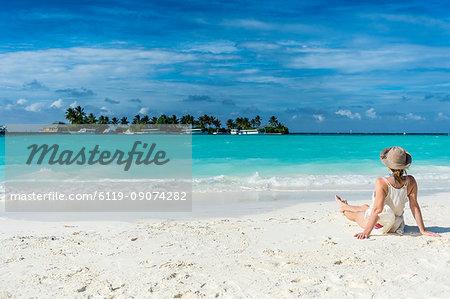 Woman sitting on a white sand beach enjoying the turquoise water, Sun Island Resort, Nalaguraidhoo island, Ari atoll, Maldives, Indian Ocean, Asia