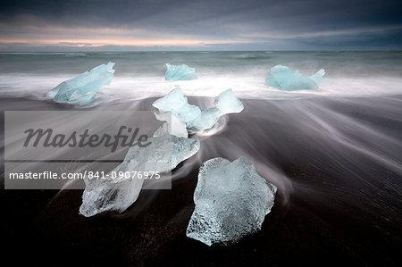 Glassy pieces of ice on volcanic black sand beach with blurred waves, near Jokulsarlon Lagoon, South Iceland, Polar Regions