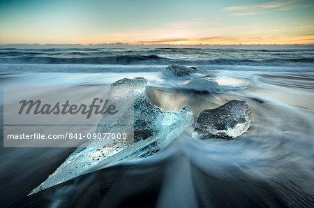Pieces of glacier ice washed up on black volcanic sand beach at sunrise, near Jokulsarlon Glacial Lagoon, South Iceland, Polar Regions