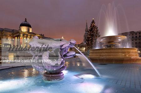 Trafalgar Square at Christmas in snow at night, London, England, United Kingdom, Europe