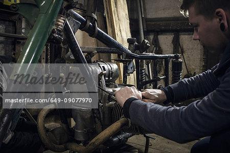 Mechanic repairing vintage motorcycle engine in workshop