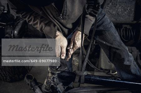 Mechanic repairing dismantled vintage motorcycle in workshop, mid section
