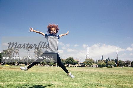 Schoolgirl doing star jump on school sports field