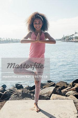 Portrait of schoolgirl practicing yoga tree pose by lakeside