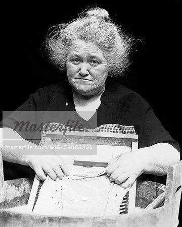 1930s DEPRESSION ERA SENIOR WOMAN SAD FACIAL EXPRESSION WASHING CLOTHES LAUNDRY ON SCRUBBING WASHBOARD LOOKING AT CAMERA