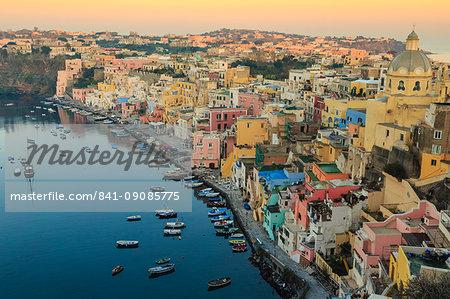 Marina Corricella at sunrise, fishing village, colourful houses, church and harbour boats, Procida Island, Bay of Naples, Campania, Italy, Europe