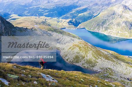 Hiker on the shore of Lago Nero admires the blue Lake Montespluga in summer, Chiavenna Valley, Valtellina, Lombardy, Italy, Europe