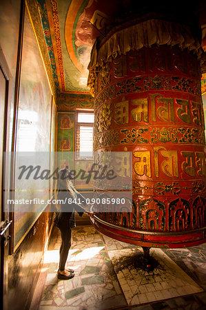 Woman praying at a Buddhist prayer wheel in Bouddha (Boudhanath) temple, UNESCO World Heritage Site, Kathmandu, Nepal, Asia