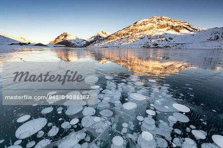 Ice bubbles at sunrise, Bianco Lake, Bernina Pass, Engadine, Switzerland, Europe