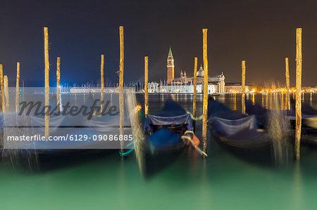 Venetian gondola moored on Grand Canal and San Giorgio Maggiore Church in background, Venice, Veneto, Italy