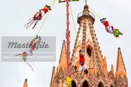 The Danza de los Voladores (Dance of the Flyers) or Palo Volador (pole flying) by the Totonac tribe performing in front of the Parroquia de San Miguel Arcangel at the St Michael Archangel Festival in San Miguel de Allende, Mexico