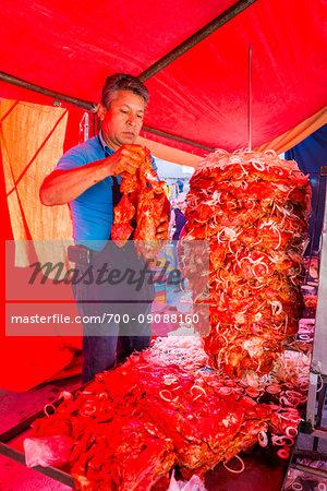 Man preparing meat on large spit inside a tent at the Tianguis de los Martes (Tuesday Market) in San Miguel de Allende, Mexico
