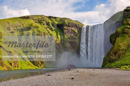 Woman staring at Skogafoss waterfall, Skogar, Sudurland, Iceland