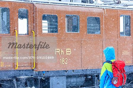 Man looks the snowplow of Bernina Express train, Ospizio Bernina, Poschiavo, canton of Graubünden, Engadin Valley, Switzerland