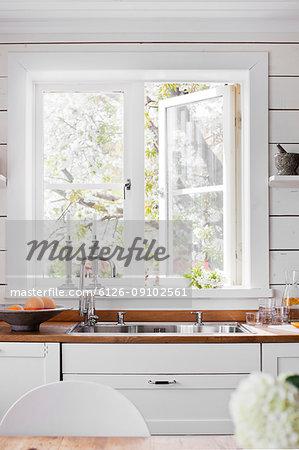 Sink by white window in domestic kitchen