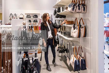 Woman choosing purse in shop