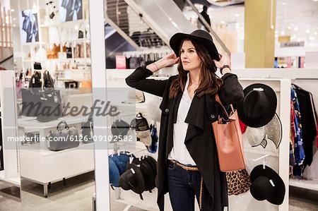 Woman choosing hat in shop