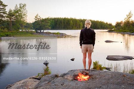 Woman standing at lake side near bonfire