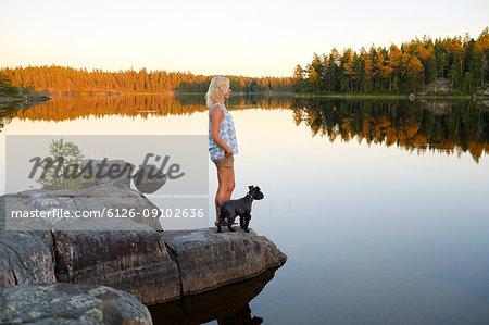 Woman and dog looking at view at lake side