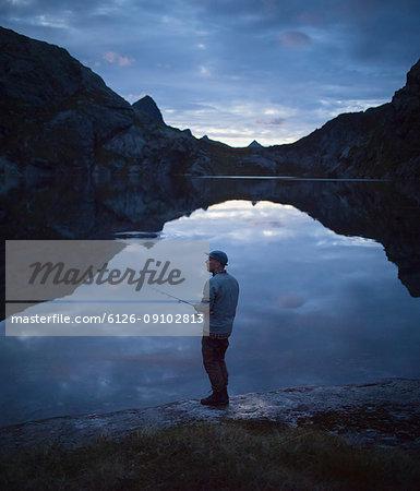Man fishing in lake Fjerddalsvatnet at dawn