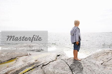 Boy standing on rocky seashore in the Stockholm archipelago