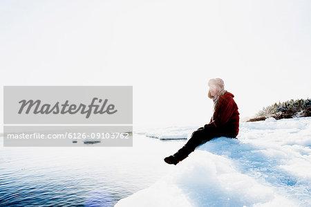 Man sitting on ice by sea in Biludden, Sweden