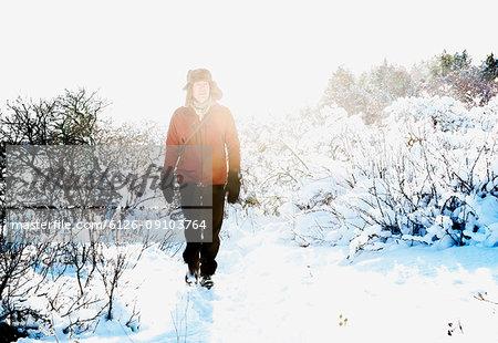 Man walking through snow in Biludden, Sweden