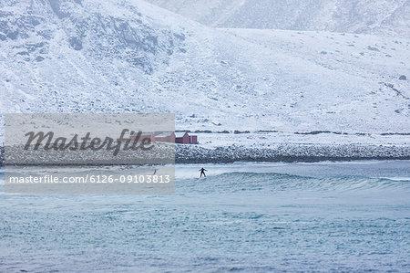 People surfing in the sea below snowy hills in Norway