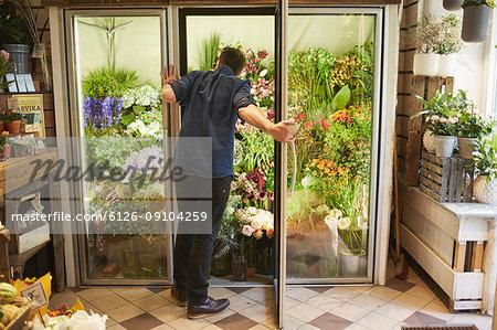 Florist opening door in flower shop