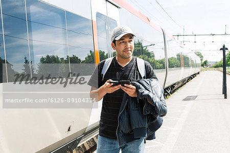 Man holding smart phone on train platform