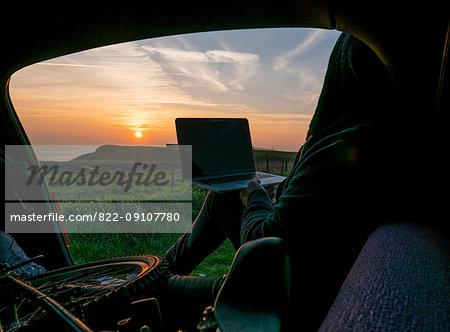 Man Sitting in Car Boot at Sunset Using Laptop Computer