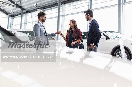Car salesman giving car keys to customers in car dealership showroom
