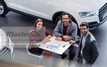Portrait smiling car sales people meeting in car dealership showroom