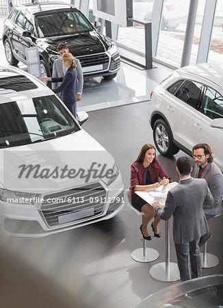 Car sales people meeting at table in car dealership showroom