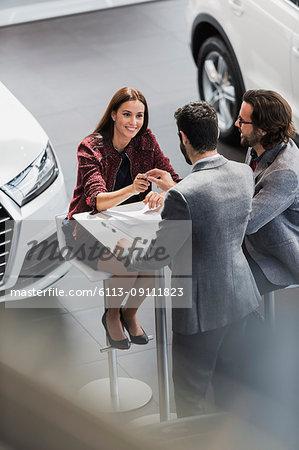 Car salesman giving car keys to smiling female customer in car dealership showroom
