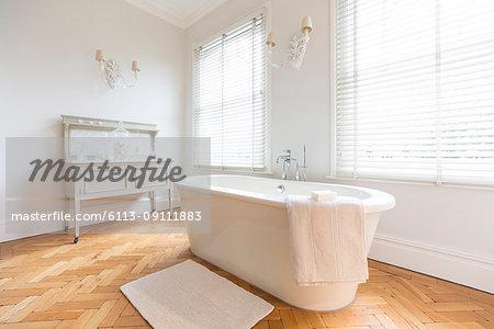 White, luxury home showcase interior bathroom with soaking tub and parquet hardwood floor