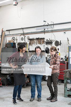 Three women standing in metal workshop, holding technical blueprint.