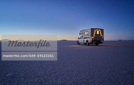 Recreational vehicle, travelling at dusk, across salt flats, Salar de Uyuni, Uyuni, Oruro, Bolivia, South America