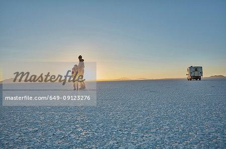 Mother and son standing on salt flats, looking at view,  Salar de Uyuni, Uyuni, Oruro, Bolivia, South America