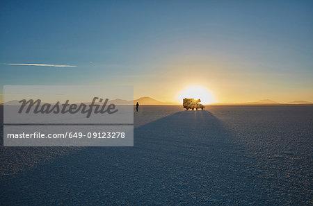Woman exploring salt flats, recreational vehicle in background, Salar de Uyuni, Uyuni, Oruro, Bolivia, South America