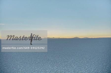 Woman standing on salt flats, looking at view, Salar de Uyuni, Uyuni, Oruro, Bolivia, South America